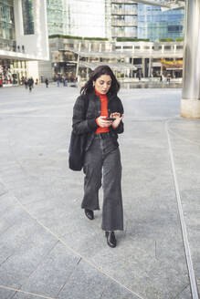 Beautiful woman using smartphone walking on a square - MEUF00281