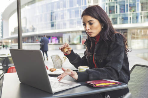 Woman using laptop having breakfast in a cafe - MEUF00287