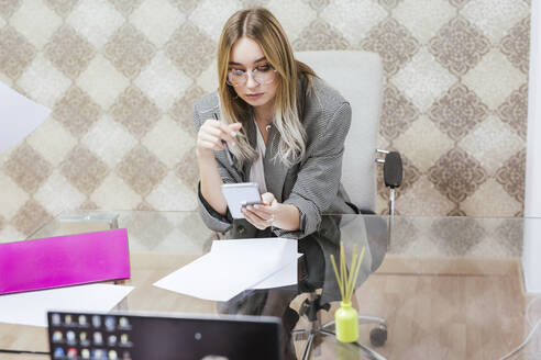 Young businesswoman using cell phone at desk in office - LJF01460