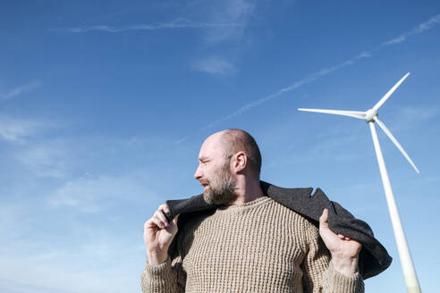 Bearded mature man against sky with wind wheel in the background - VYF00072