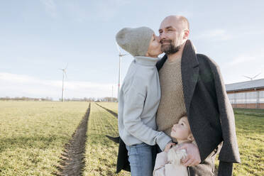 Happy parents with little daughter standing on a field in winter - VYF00075
