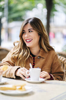 Portrait of happy young woman at an outdoor cafe - DGOF00558