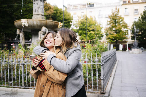 Two happy young women hugging in the city - DGOF00564