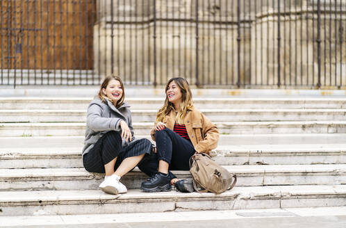 Two happy young women sitting on stairs in the city - DGOF00570