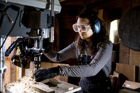Woman with long brown hair wearing dungarees, safety glasses and ear protectors standing in wood workshop, using electric drill. - MINF14460