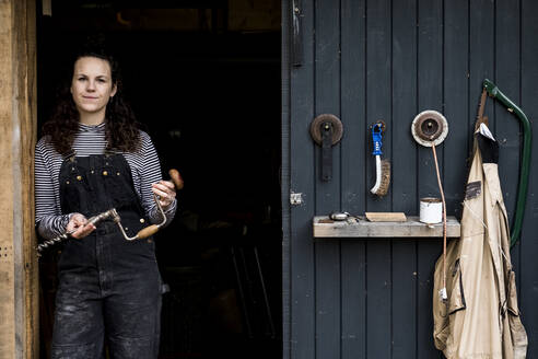 Woman with long brown hair wearing dungarees standing at entrance to wood workshop, looking at camera. - MINF14484