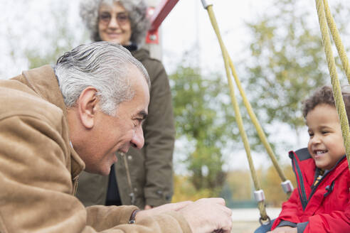 Grandfather playing with grandson on swing at playground - CAIF24523