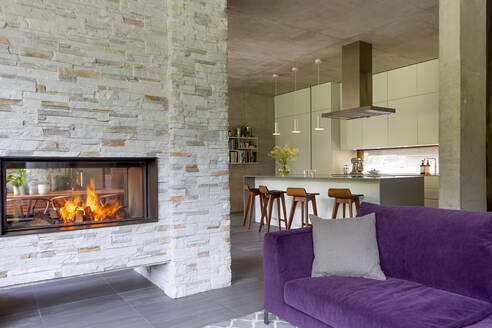 Modern living room with brick fireplace open to kitchen - CAIF24688