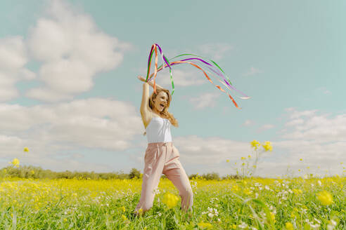 Happy young woman moving with colourful ribbons in a flower meadow in spring - ERRF02886