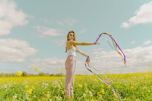 Young woman standing with colourful ribbons in a flower meadow in spring - ERRF02889