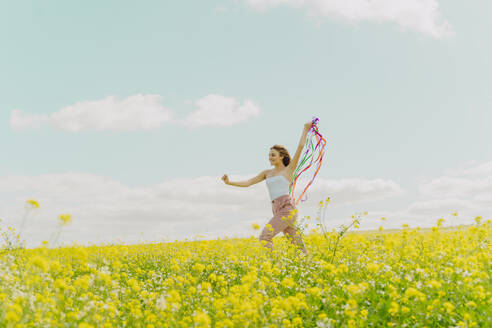 Happy young woman moving with colourful ribbons in a flower meadow in spring - ERRF02901