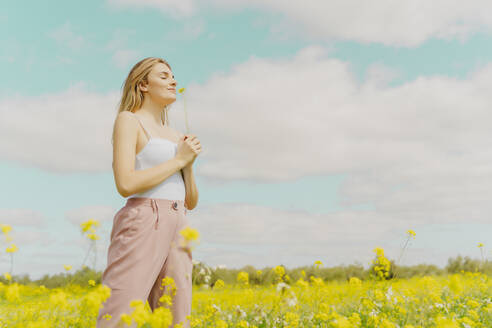 Young woman standing in a meadow in spring holding a flower - ERRF02904