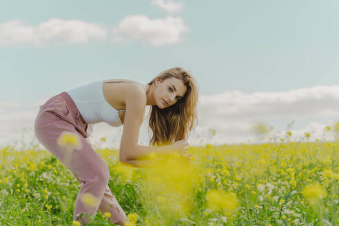 Portrait of young woman in a flower meadow in spring - ERRF02916