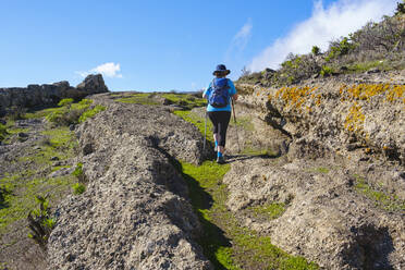 Spain, Province of Santa Cruz de Tenerife, San Sebastian de La Gomera, Rear view of senior backpacker hiking along rocky trail - SIEF09669