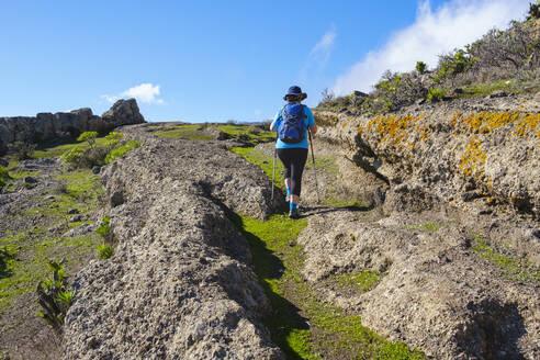 Spain, Province of Santa Cruz de Tenerife, San Sebastian de La Gomera, Rear view of senior backpacker hiking along rocky trail - SIEF09669