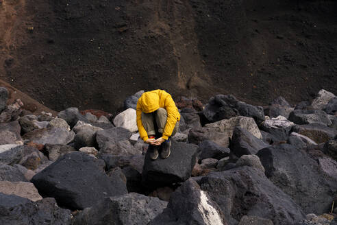 Man crouching amidst volcanic rocks, Sao Miguel Island, Azores, Portugal - AFVF05833