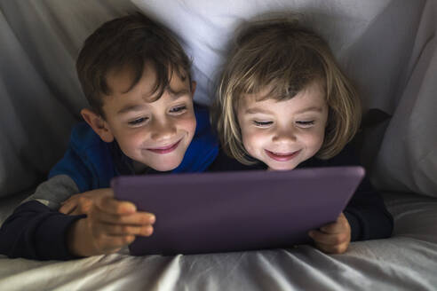 Portrait of happy brother and little sister lying side by side under a blanket using digital tablet - JRFF04237