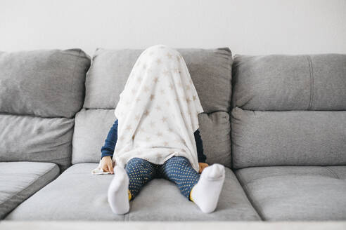 Little girl sitting on the couch at home hiding under blanket - JRFF04249
