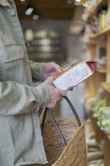 Close-up of senior man buying groceries in a small food store checking ingredients - AFVF05846