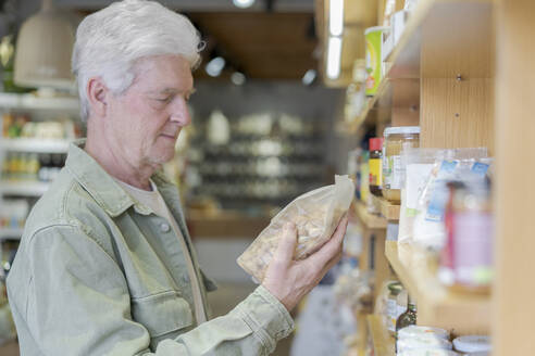 Senior man buying groceries in a small food store - AFVF05849