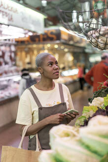 Woman buying groceries in a market hall - AFVF05888