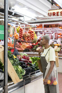 Woman buying groceries in a market hall - AFVF05900