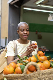 Woman buying tangerines in a market hall - AFVF05909