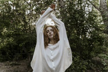 Young redhaired woman wearing baggy shirt in forest, raising arms - AFVF05918