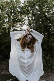 Young redhaired woman wearing baggy shirt in forest - AFVF05921