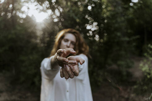 Young red-haired woman reaching out her hands in the forest - AFVF05924