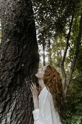 Young redhaired woman hugging tree trunk in the forest - AFVF05930