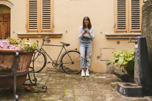 Smiling young woman standing at a house using smartphone, Greve in Chianti, Tuscany, Italy - JPIF00563