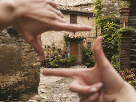 Woman finger framing a house in picturesque old town, Greve in Chianti, Tuscany, Italy - JPIF00572