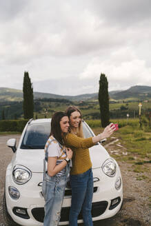 Two happy young women standing beside car taking a selfie, Tuscany, Italy - JPIF00584