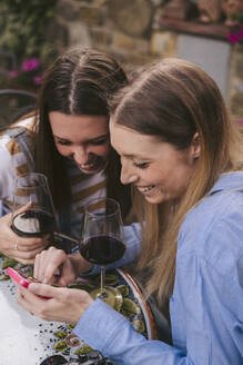 Two happy women having a glass of red wine and looking at cell phone outdoors - JPIF00590