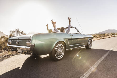 Happy couple with raised arms in convertible car on a road trip - SDAHF00687