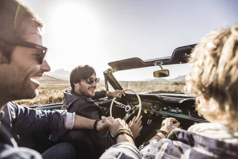 Happy friends in convertible car on a road trip - SDAHF00729