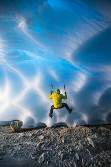 Rear view of man ice climbing in glacier cave. - CAVF77927