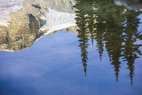 Reflection of mountain and trees in calm alpine lake. - CAVF77939