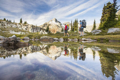 Reflection of backpackers hiking beside alpine lake in mountains. - CAVF77945