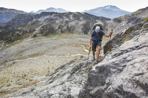 Backpacker hikes across talus slope in mountains near Whistler. - CAVF77951