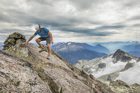 Climber carefully hikes off the summit of a mountain. - CAVF77963