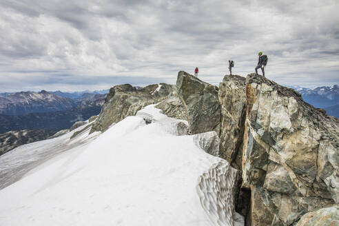 Three climbers stand on a rocky summit above snow covered glacier. - CAVF77966