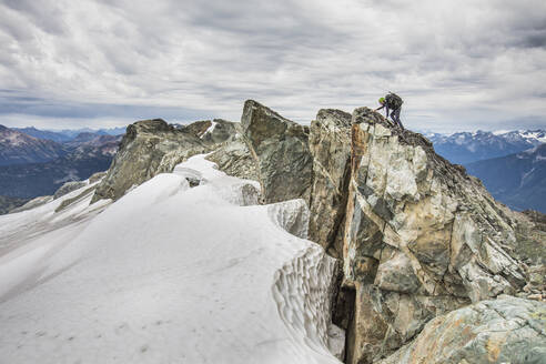 Climber approaches summit of a rocky mountain peak. - CAVF77969