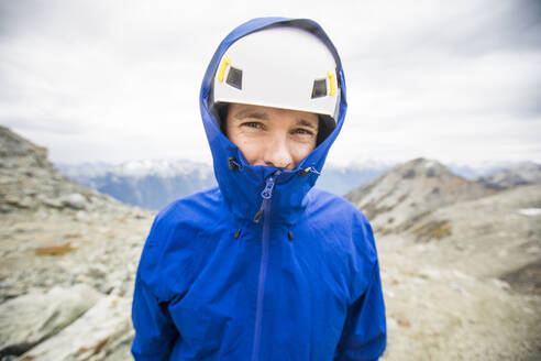 Portrait of mountain climber wearing helmet and rain jacket. - CAVF77972