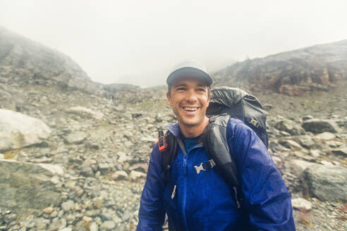 Backpacker smiling despite bad weather, rain and wind. - CAVF77984