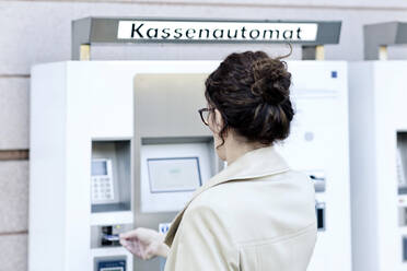 Back view of mature woman using pay machine - FLLF00437