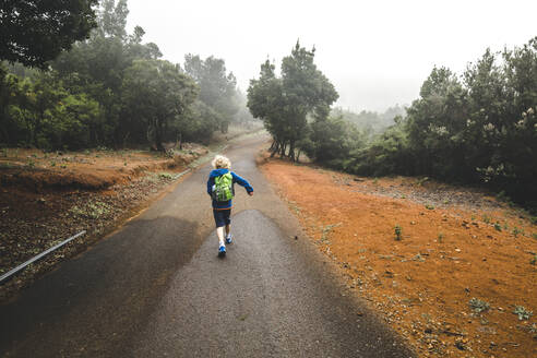 Back view of little boy with backpack  walking on country road, La Gomera, Canary Islands, Spain - IHF00291