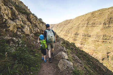 Back view of father and little son with backpacks walking on a hiking trail in the mountains, La Gomera, Canary Islands, Spain - IHF00294