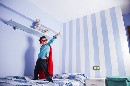 Little boy playing super hero, standing on his bed - LJF01481
